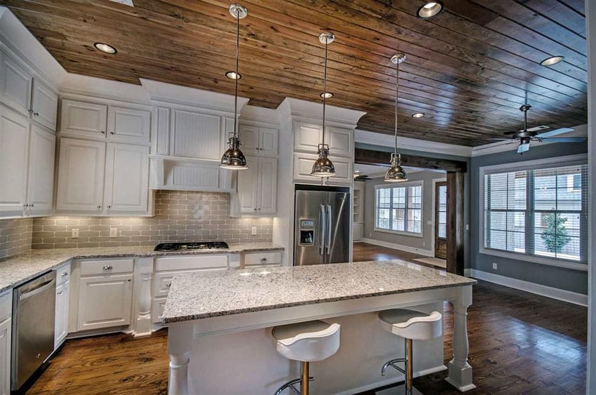 Rustic kitchen with white cabinets, snowfall granite counter and breakfast bar island with chrome pendant lighting
