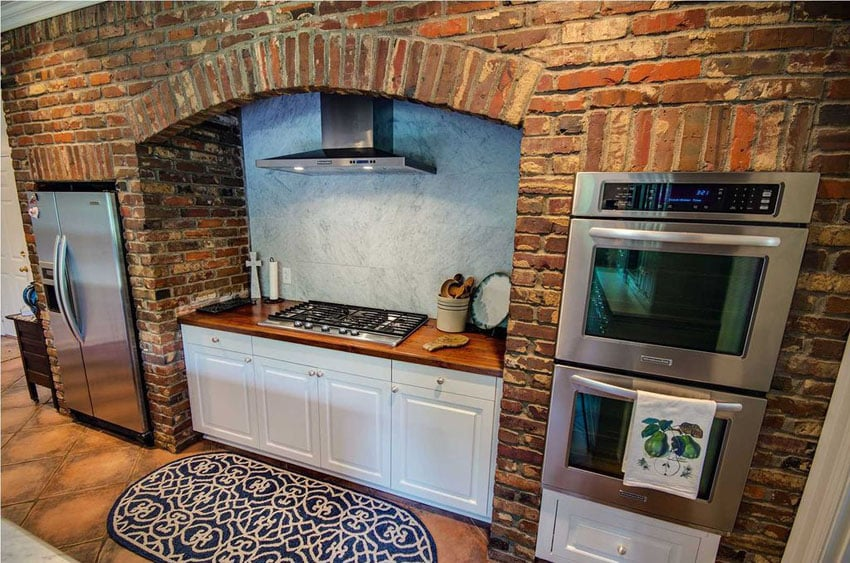 Rustic one wall kitchen with brick surround and white cabinets