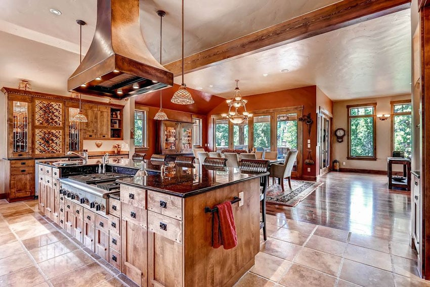 Rustic open concept kitchen with island range and custom cabinetry