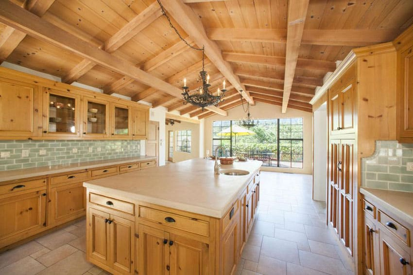 Rustic wood kitchen with marble countertops, arched beam ceiling and green glass subway tile