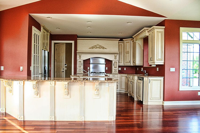 Traditional kitchen with painted cream color decorative cabinetry, granite peninsula and red walls