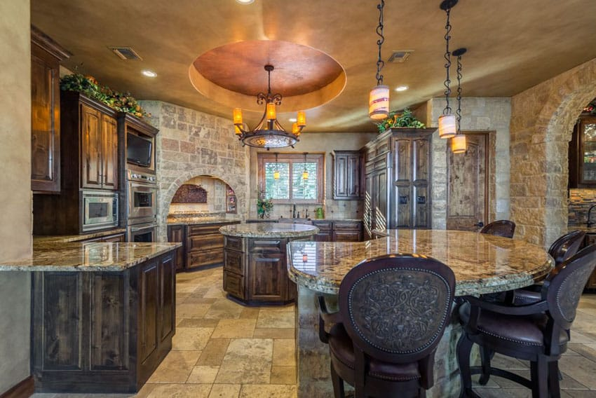 Traditional kitchen with rustic cabinets, cupola ceiling with wrought iron chandelier and curved breakfast bar granite island