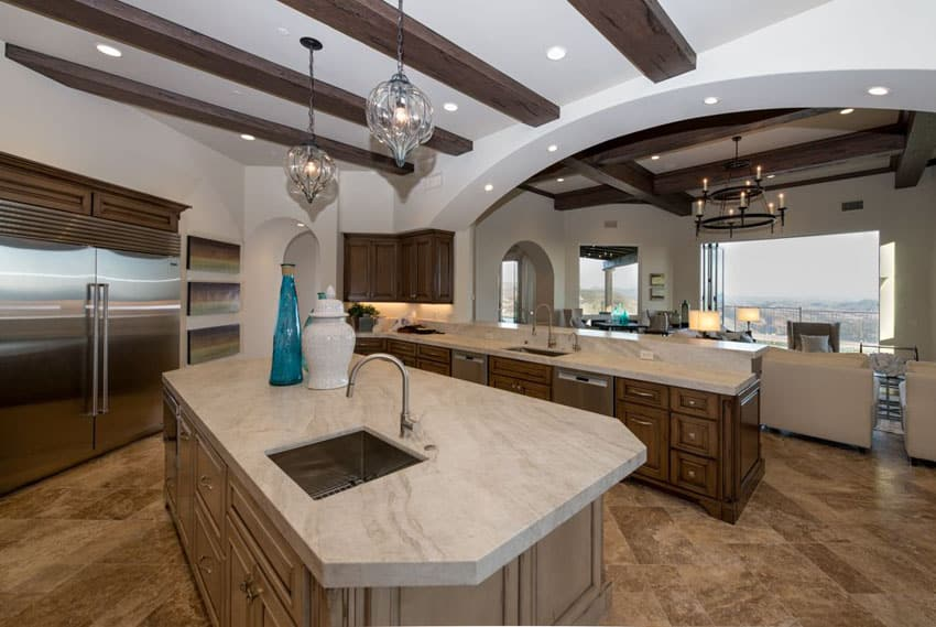 Traditional kitchen with custom designed island with built in sink arched walls and exposed beam ceiling