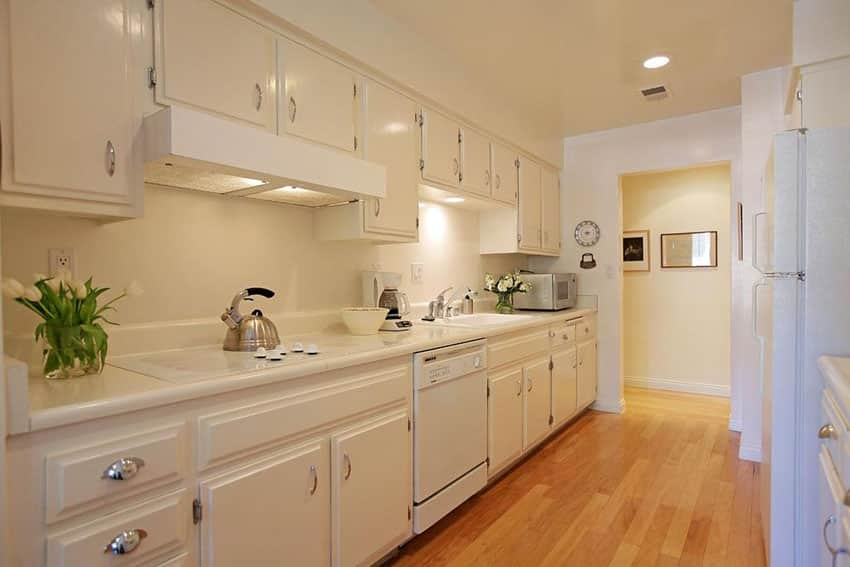 Traditional single line kitchen with corian solid surface counter, white cabinets and pecan engineered wood floors