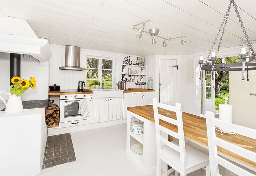 White farmhouse kitchen with rustic dining table and large double basin sink