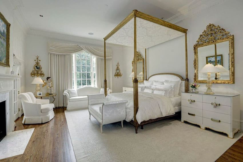 White theme french style bedroom with four poster bed in gold with white bed seat and furniture