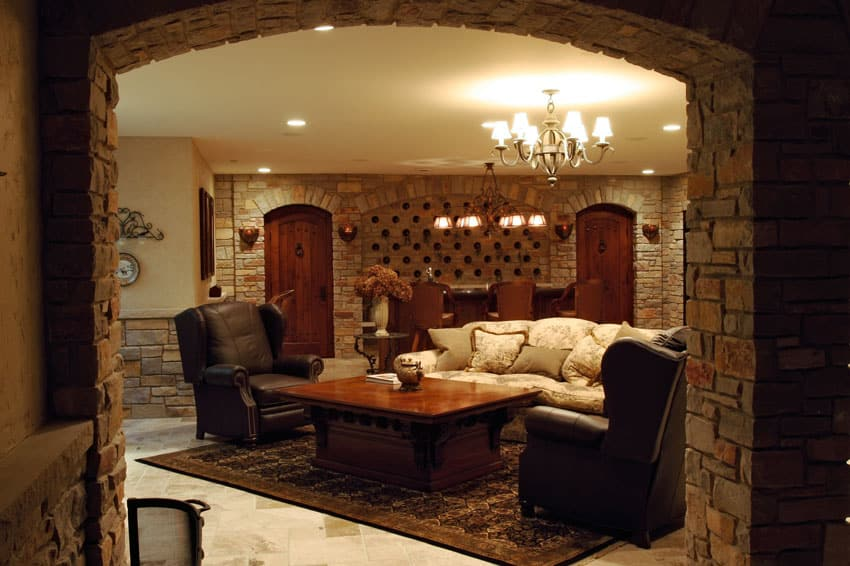 Basement lounge with custom stone walls and home bar