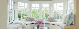 beautiful-bay-window-seat-with-comfy-cushions-and-wood-table