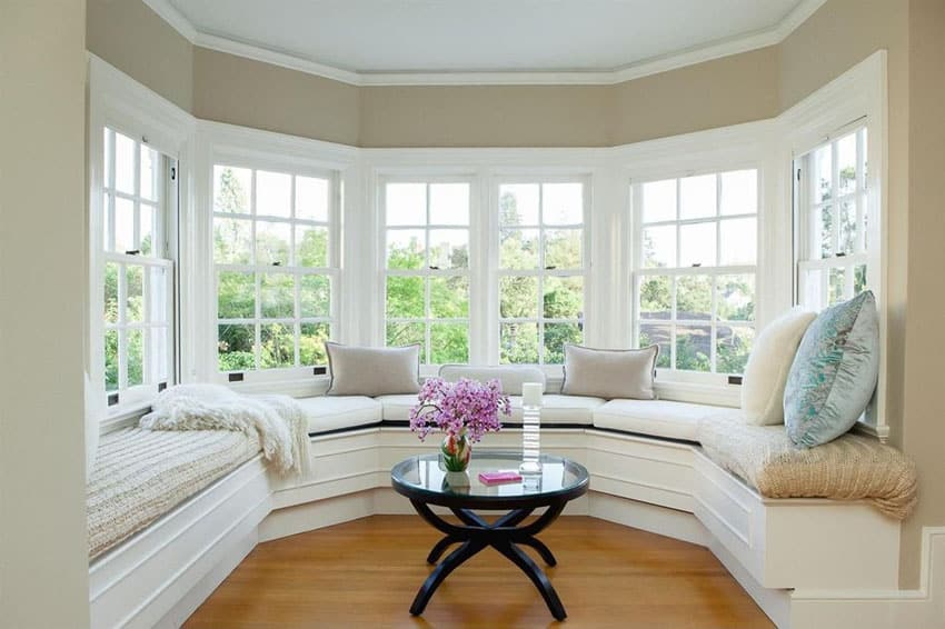 Beautiful bay window seat with comfy cushions and wood table