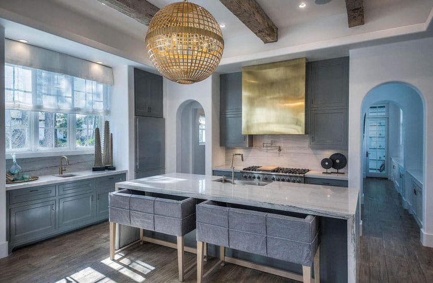 Beautiful contemporary kitchen dark blue cabinets and calacatta lasa marble, large gold pendant light and two seater benches