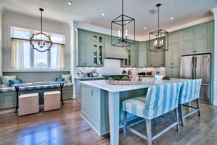 Beautiful cottage kitchen with aqua blue cabinets, breakfast bar island, white marble counters and window seat bench