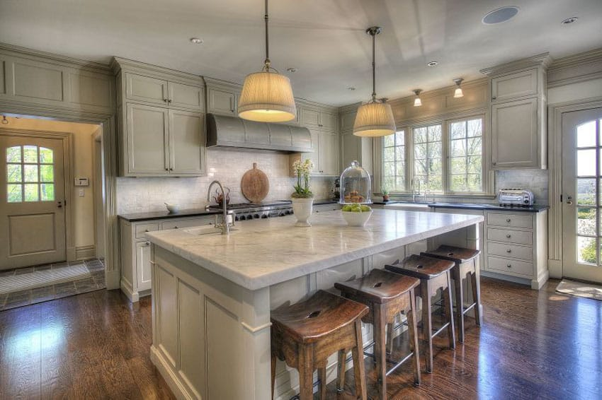 Beautiful cottage kitchen with carrara marble counter and large island with wood flooring