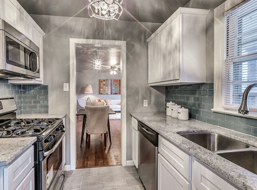 Beautiful small galley kitchen with white cabinets, juparana delicatus granite and porcelain tile floors