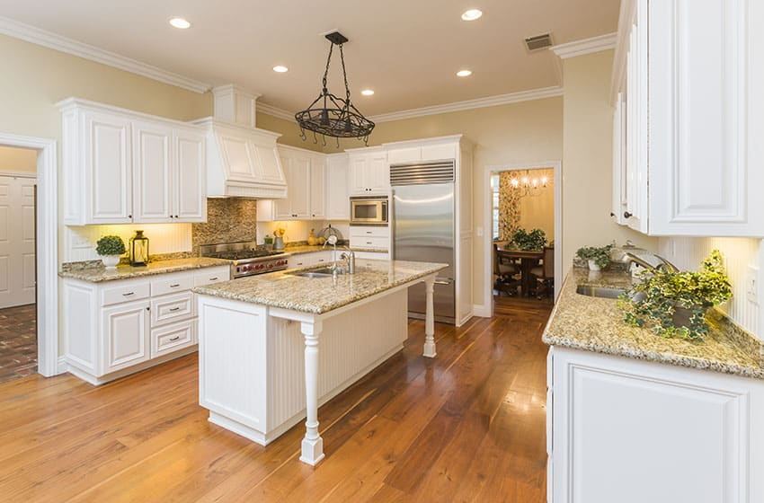 Beautiful white country style kitchen with yellow granite counter and island with sink