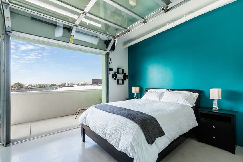 Bedroom with roll up door teal accent wall balcony and city views