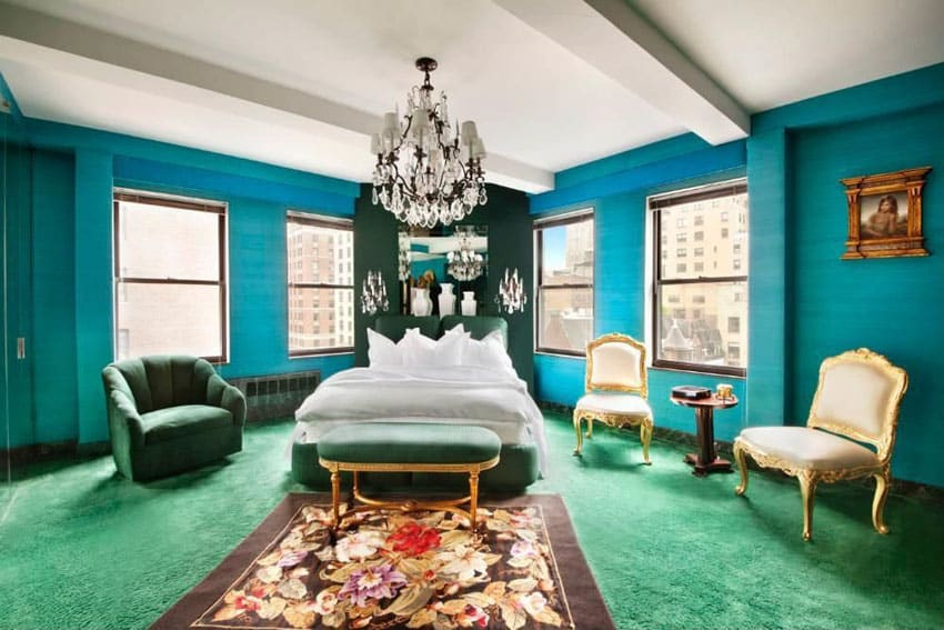 Bedroom with teal walls, chandelier and green carpet