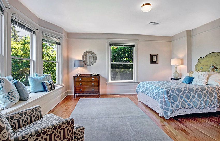 Bedroom with white window seat and red oak hardwood floors