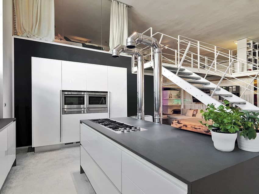 Black and white modern kitchen in loft apartment with high ceilings
