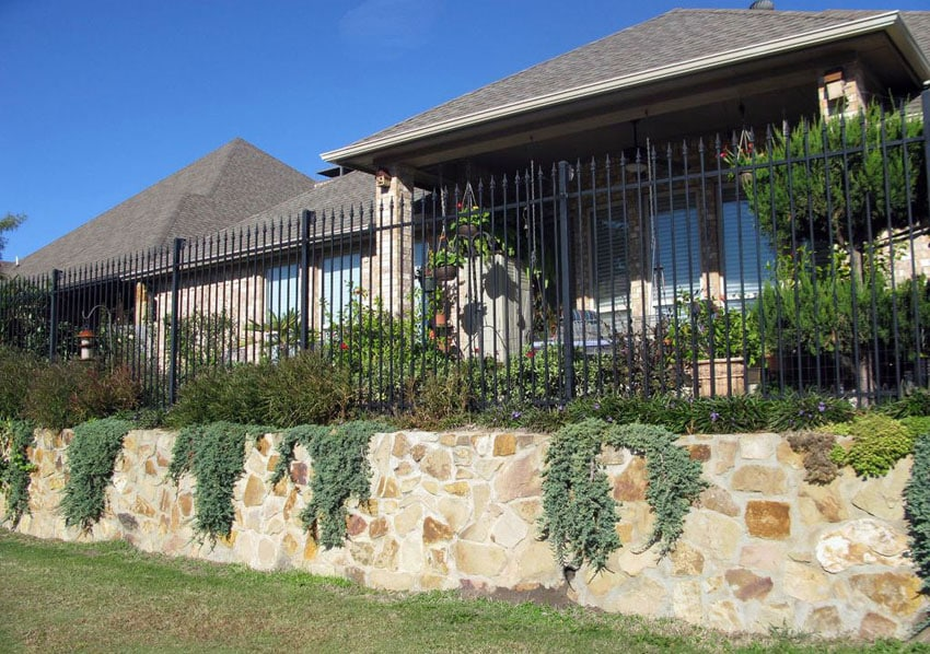 Black wrought iron fence and stone retaining wall
