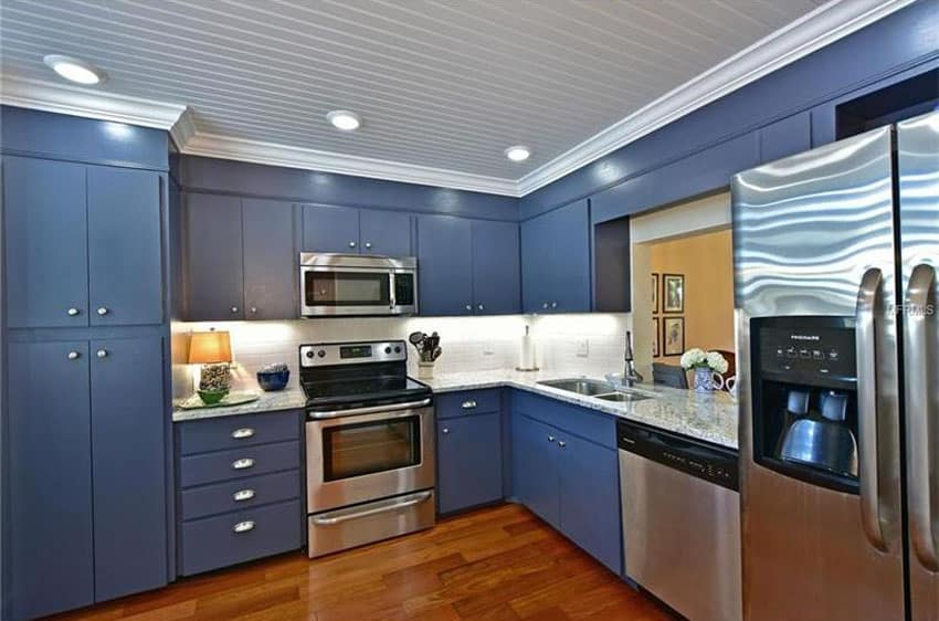 Blue cabinet kitchen with white moldings and blanco tulum granite counters
