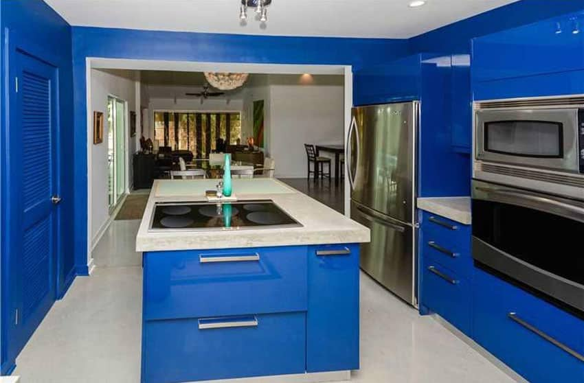 Bright blue modern kitchen with glossy cabinets and island with concrete counters