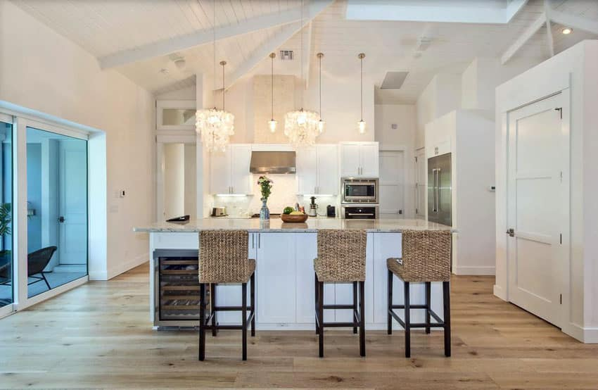 Bright cottage kitchen with white cabinets and light wood flooring