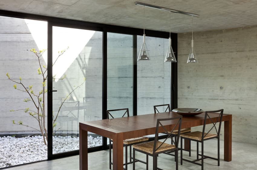 Concrete dining room with wood table and glass pendant lights