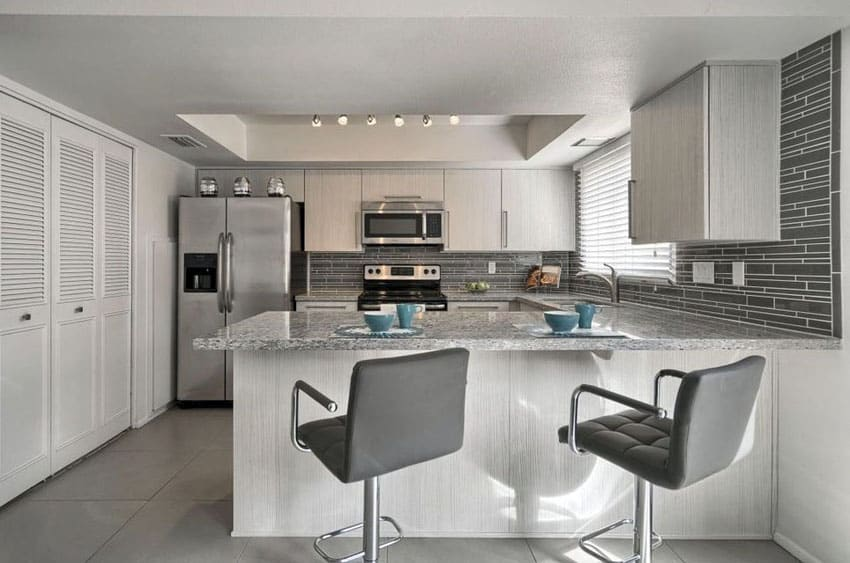 Contemporary kitchen with peninsula, white cabinets and gray mosaic tile backsplash