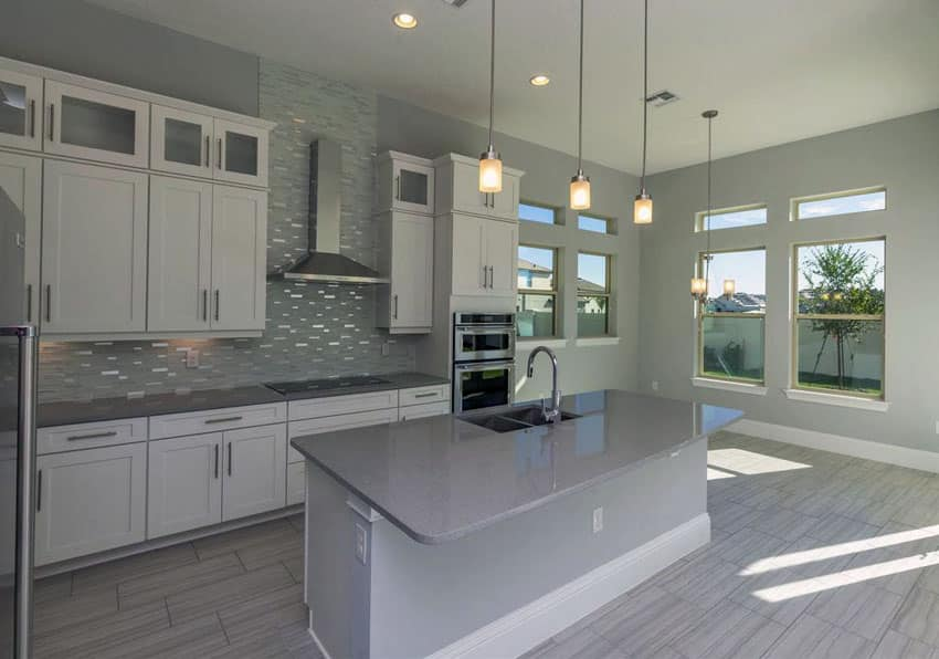Contemporary kitchen with white cabinets, gray island counter, pendant lighting and gray backsplash