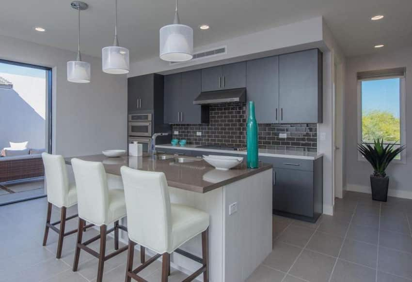 Contemporary kitchen with white island and dark gray cabinets with porcelain tile flooring
