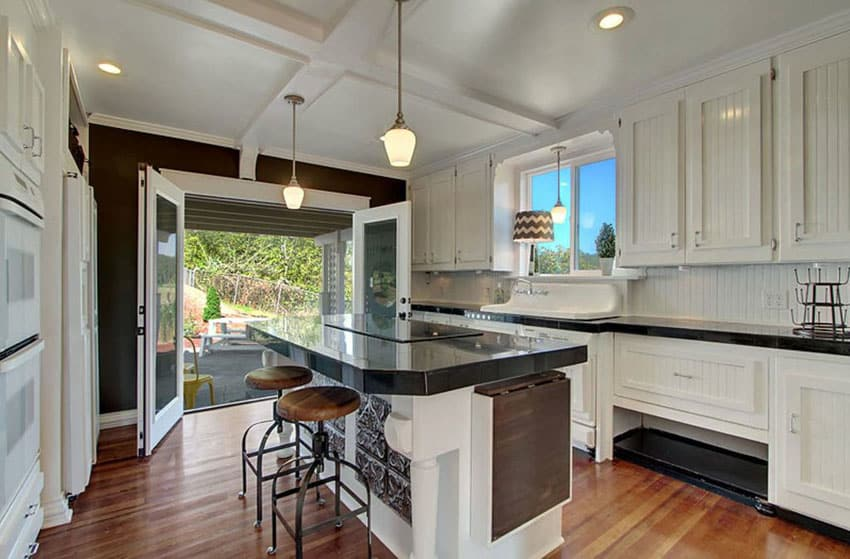Cottage kitchen with beadboard cabinets, wood floors and eat in dining island