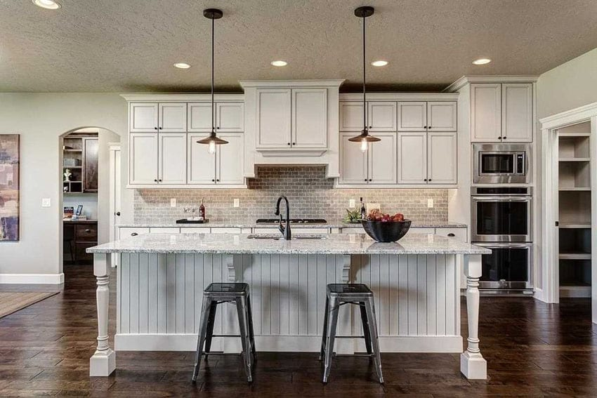 Cottage kitchen with large island, white granite counters and dark wood floors