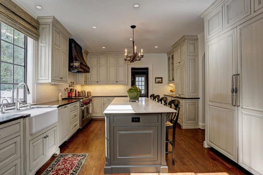 Cottage kitchen with off white cabinets and marble counter island