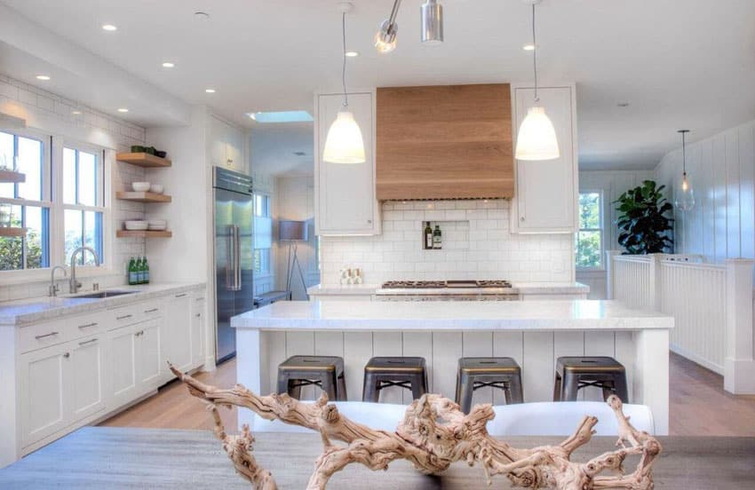 Cottage kitchen with white cabinets, white tile backsplash and long breakfast bar island