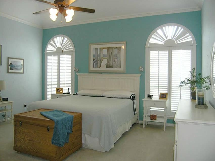 Cottage style bedroom with white and blue theme with curved decorative windows and plantation shutters
