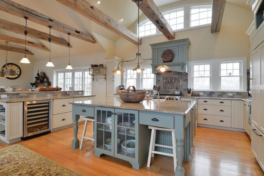 Country kitchen with exposed beams, white cabinets and painted island with blanco tulum granite counters