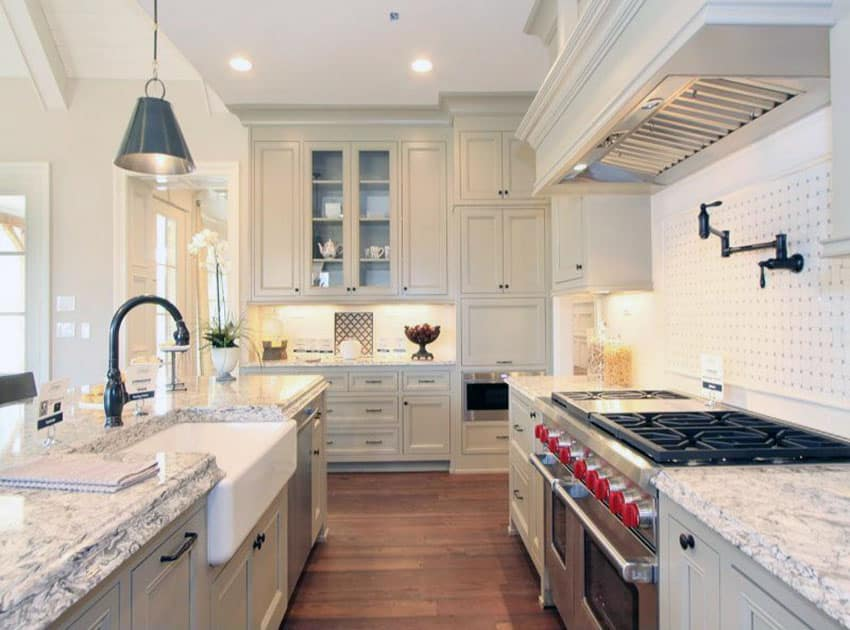 Country style galley kitchen with white cabinets, farmhouse sink and subzero wolf range