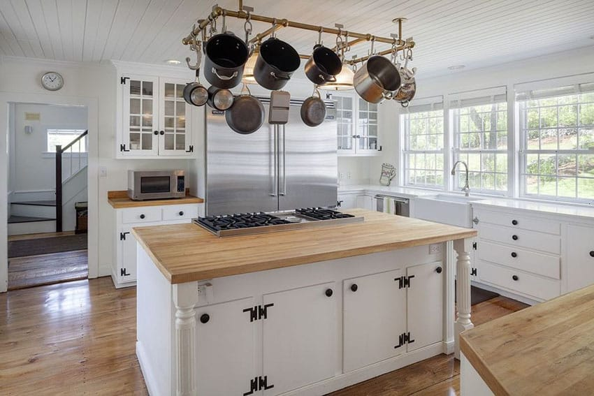 Country kitchen with white glass panel cabinets, maple wood countertops and island with built in range