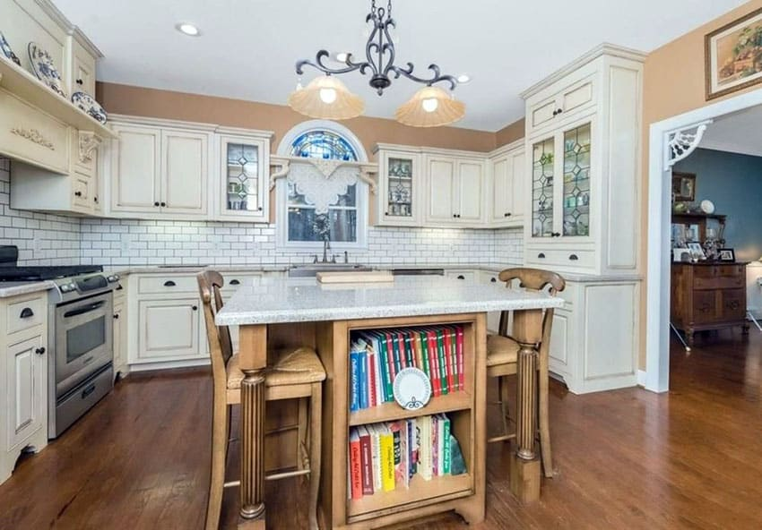 Country kitchen with white raised panel cabinets, wood center island with book storage and classic white subway tile
