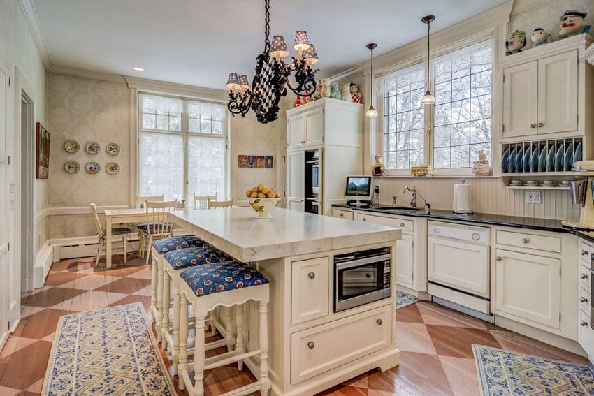 Country kitchen with white shaker cabinets, island with barstools and santorini white marble