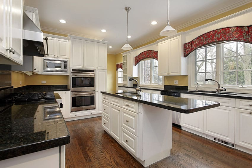 Country style kitchen design with white cabinets, black granite counters and island with overhanging counter