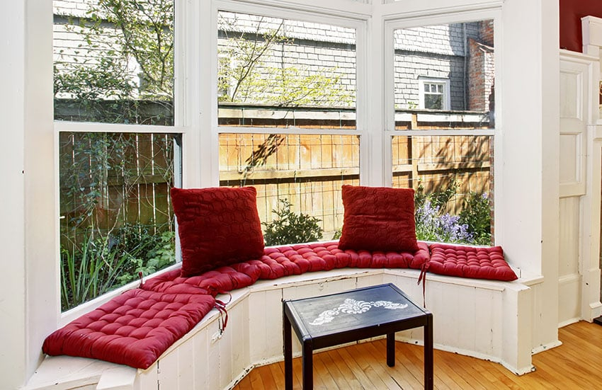 Curved window seat with red cushions