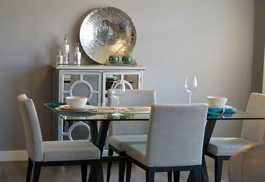 Dining room with gray contemporary chairs and glass table