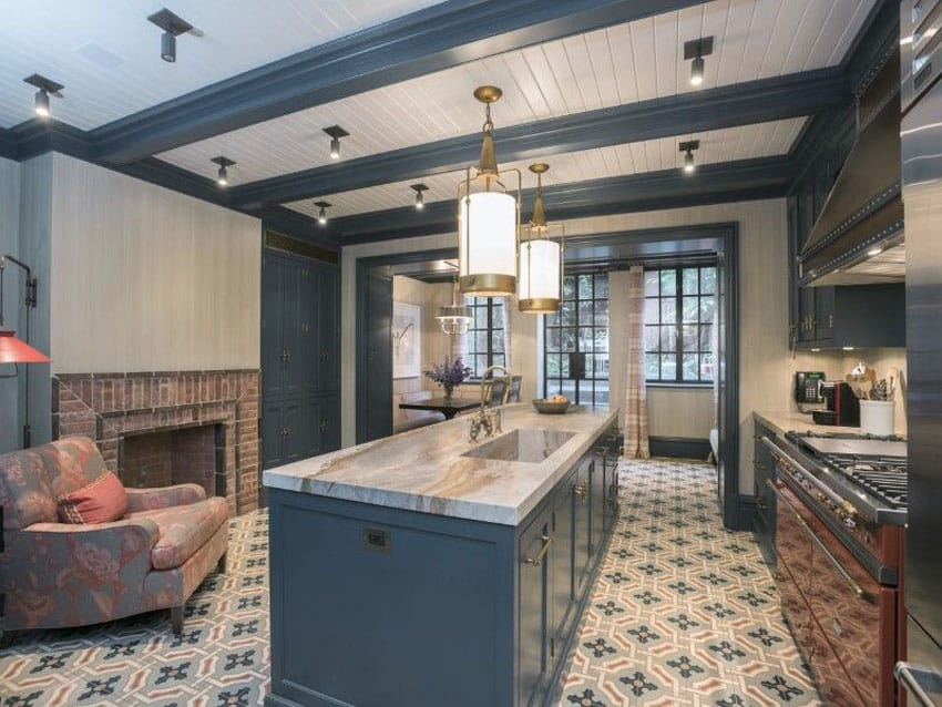 Elegant kitchen with dark blue cabinets, white marble counters and brick fireplace
