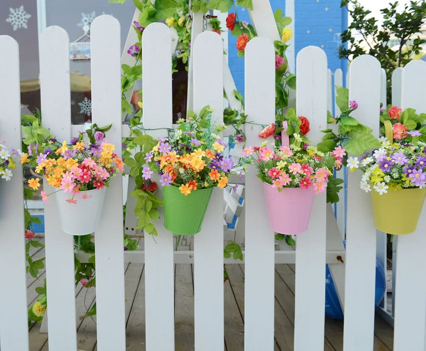 Flower pots hanging from white fence