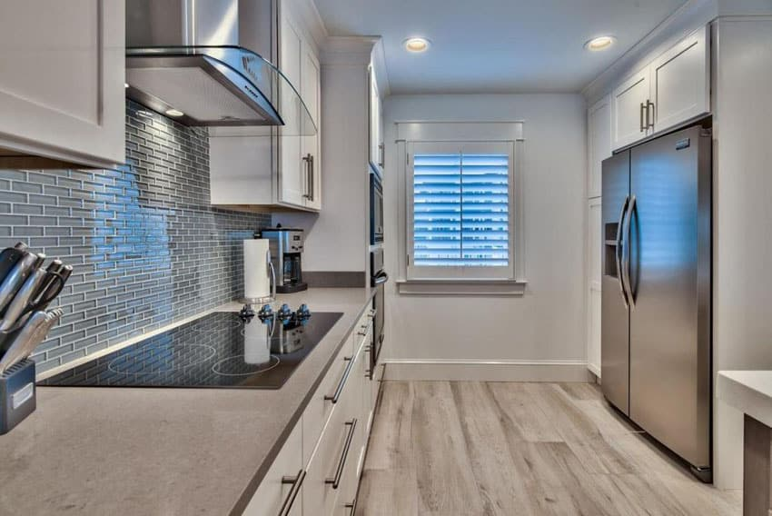 Galley kitchen with white cabinets, blue glass mosaic tile backsplash and tundra gray marble counters