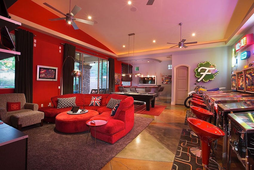 Game room man cave with red furniture, pool table and pinball machines