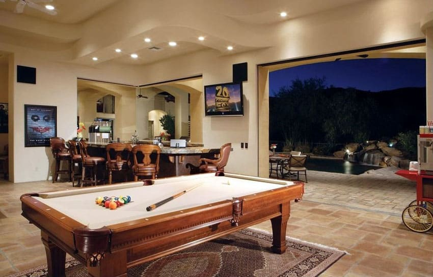 Game room with home bar open to backyard and swimming pool
