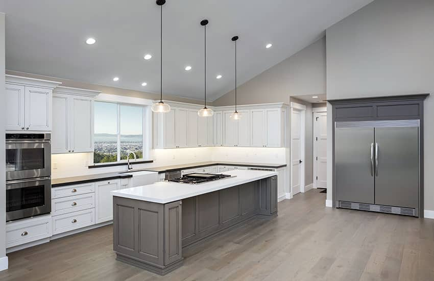 Gray and white kitchen with large island pendant lights and vaulted ceiling