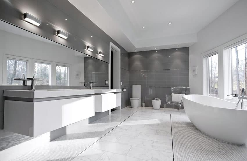 Gray and white modern bathroom with carrara marble flooring and resin tub